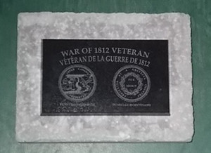 1812 Veteran Plaque mounted on retaining wall cap.